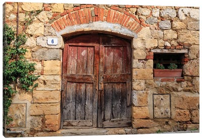 Italy, Monteriggioni. Stone wall, wooden door with planted geraniums. Canvas Art Print