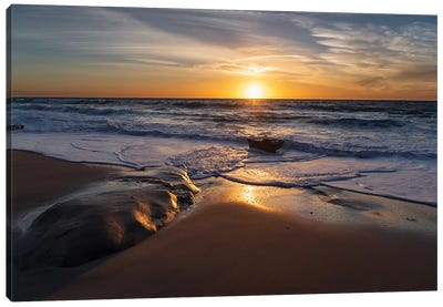 Sunset reflecting off the water on the sand of a beach Canvas Art Print