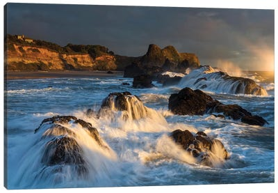 Waves crashing on rocks and washing down the sides at sunset Canvas Art Print