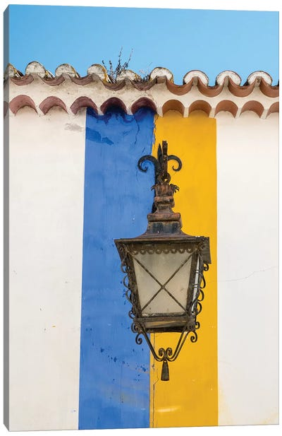 Portugal, Obidos. Wrought iron lantern hanging from a colorful stripped wall in the walled town. Canvas Art Print
