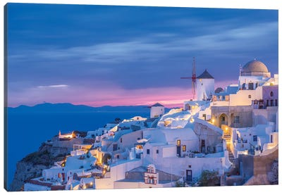 Greece, Oia. Greek Orthodox church and village at sunset.  Canvas Art Print