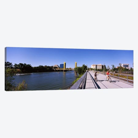 Bicyclists along the Sacramento River with Tower Bridge in background, Sacramento, Sacramento County, California, USA Canvas Print #PIM10673} by Panoramic Images Canvas Art Print