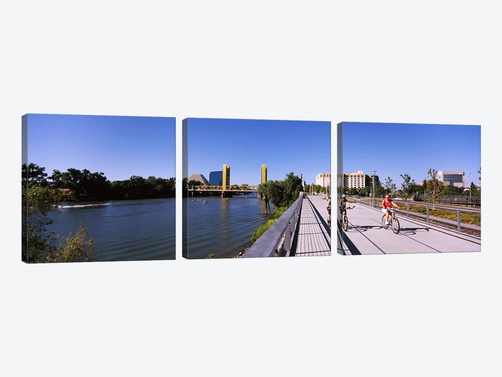 Bicyclists along the Sacramento River with Tower Bridge in background, Sacramento, Sacramento County, California, USA by Panoramic Images 3-piece Canvas Art