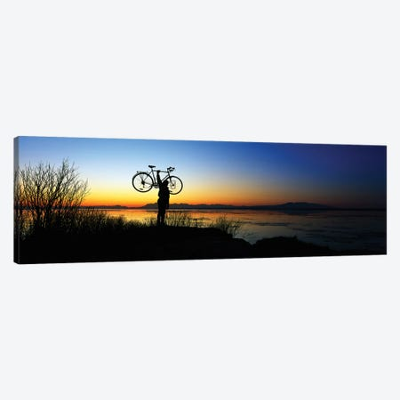 Silhouetted cyclist holding bicycle over head, river's edge, sunset, Alaska. Canvas Print #PIM12465} by Panoramic Images Canvas Artwork