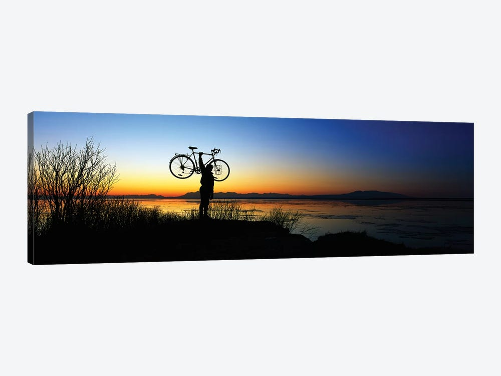 Silhouetted cyclist holding bicycle over head, river's edge, sunset, Alaska. by Panoramic Images 1-piece Canvas Art