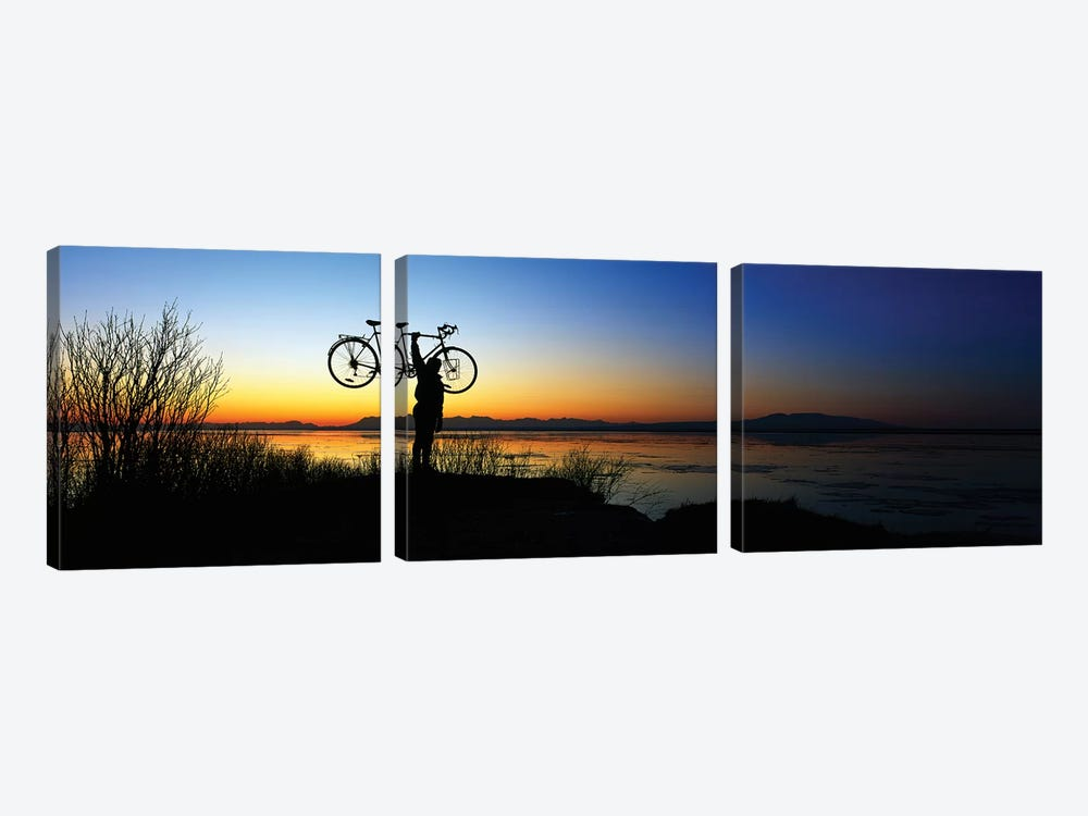 Silhouetted cyclist holding bicycle over head, river's edge, sunset, Alaska. by Panoramic Images 3-piece Canvas Wall Art