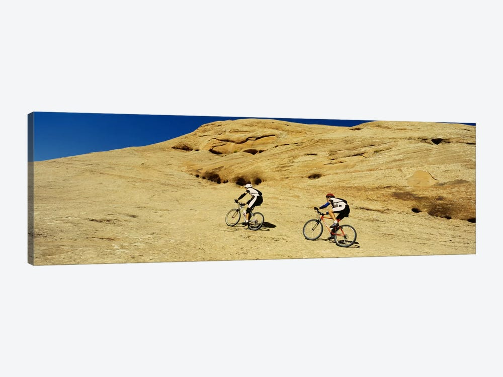 Side profile of two men mountain bilking on rocks, Slickrock Trail, Moab, Utah, USA by Panoramic Images 1-piece Canvas Art Print