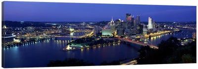 Buildings along a river lit up at dusk, Monongahela River, Pittsburgh, Allegheny County, Pennsylvania, USA Canvas Art Print