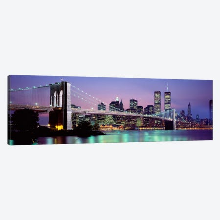 An Illuminated Brooklyn Bridge With Lower Manhattan's Financial District Skyline In The Background, New York City, New York  Canvas Print #PIM2259} by Panoramic Images Canvas Artwork