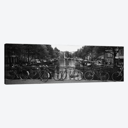 Bicycle Leaning Against A Metal Railing On A Bridge, Amsterdam, Netherlands Canvas Print #PIM3807} by Panoramic Images Canvas Art Print