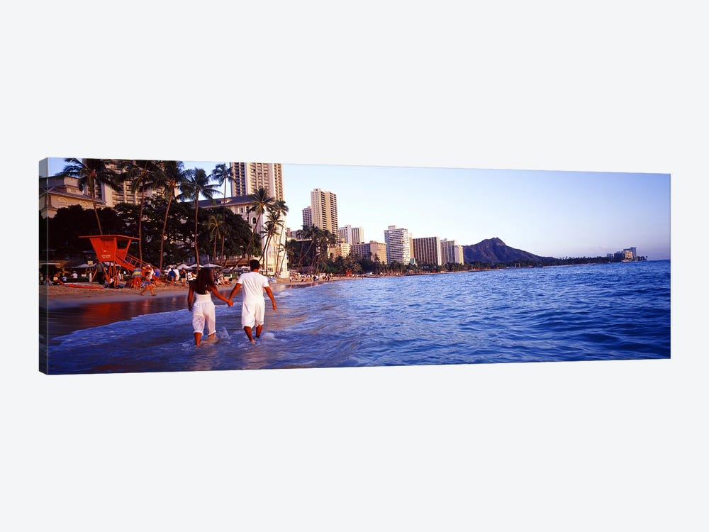 Rear view of a couple wading on the beach, Waikiki Beach, Honolulu, Oahu, Hawaii, USA by Panoramic Images 1-piece Canvas Print