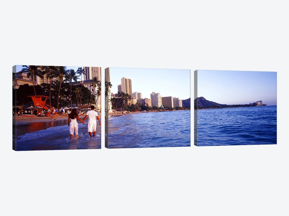 Rear view of a couple wading on the beach, Waikiki Beach, Honolulu, Oahu, Hawaii, USA by Panoramic Images 3-piece Art Print