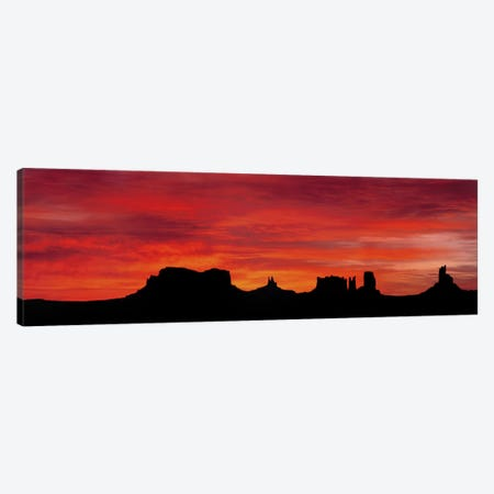 Silhouette Of Monument Valley's Buttes Across A Deep Orange Sunset Canvas Print #PIM4566} by Panoramic Images Canvas Print