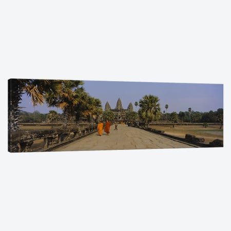 Two monks walking in front of an old temple, Angkor Wat, Siem Reap, Cambodia Canvas Print #PIM5884} by Panoramic Images Canvas Print