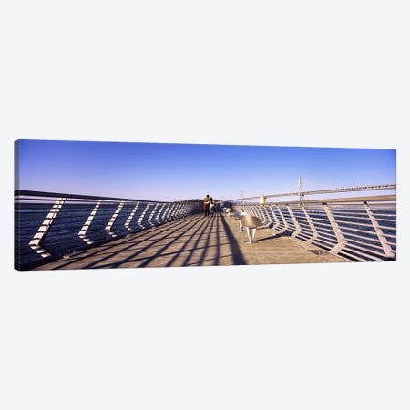 Couple walking on a pier, Bay Bridge, San Francisco, California, USA Canvas Print #PIM6457} by Panoramic Images Canvas Artwork