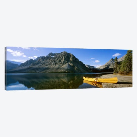 Crowfoot Mountain With A Lone Canoe On The Shore Of Bow Lake, Banff National Park, Alberta, Canada Canvas Print #PIM6618} by Panoramic Images Canvas Art Print