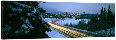 Autumobile lights on busy street, distant city lights, frozen Westchester Lagoon, Anchorage, Alaska, USA. Canvas Art Print
