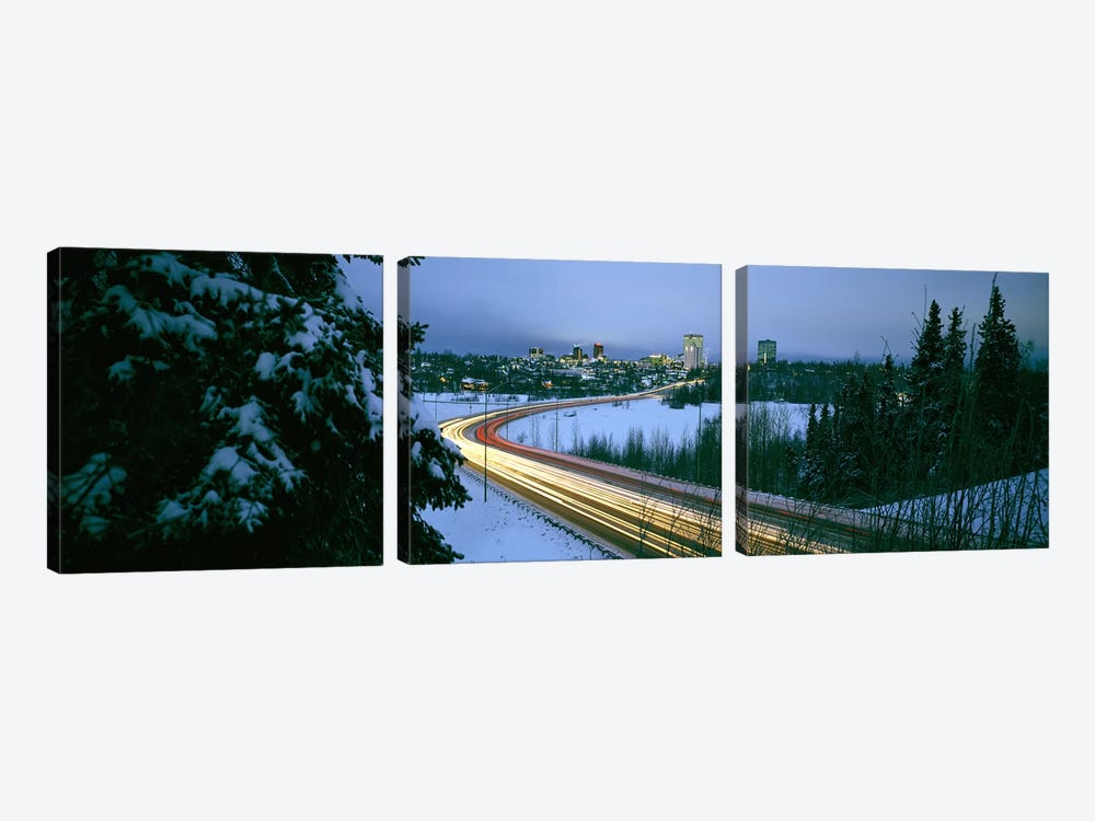Autumobile lights on busy street, distant city lights, frozen Westchester Lagoon, Anchorage, Alaska, USA. by Panoramic Images 3-piece Canvas Art Print