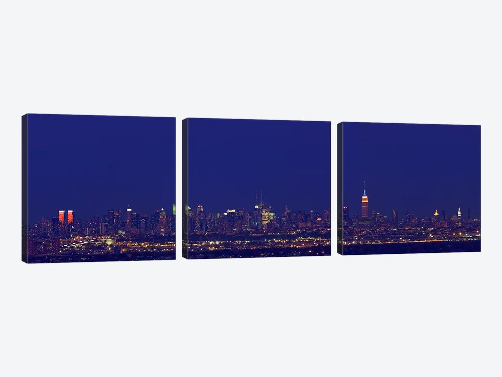 Buildings in a city lit up at night, New York City, New York State, USA by Panoramic Images 3-piece Art Print