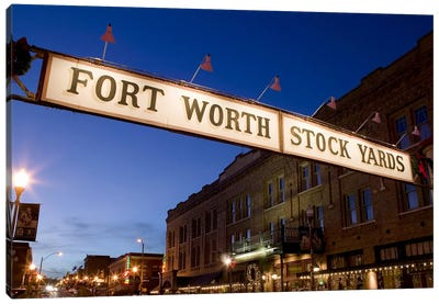 Signboard over a road at dusk, Fort Worth Stockyards, Fort Worth, Texas, USA Canvas Art Print
