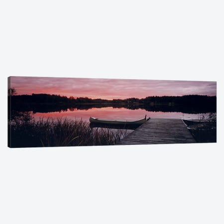 Canoe tied to dock on a small lake at sunset, Sweden Canvas Print #PIM9782} by Panoramic Images Art Print