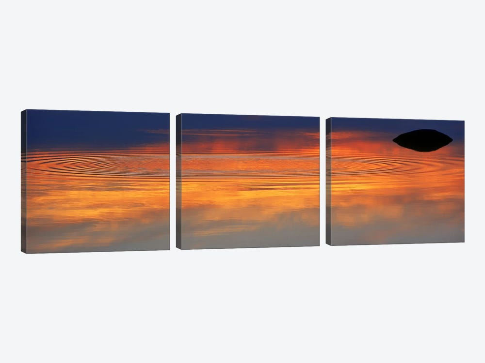Reflection of clouds with circular ripples spreading outward across glassy lake waters at sunset by Panoramic Images 3-piece Canvas Wall Art