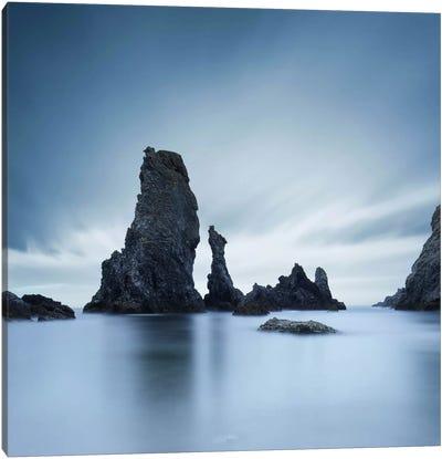 Dark rocks in a blue ocean under cloudy sky in a bad weather. Canvas Art Print