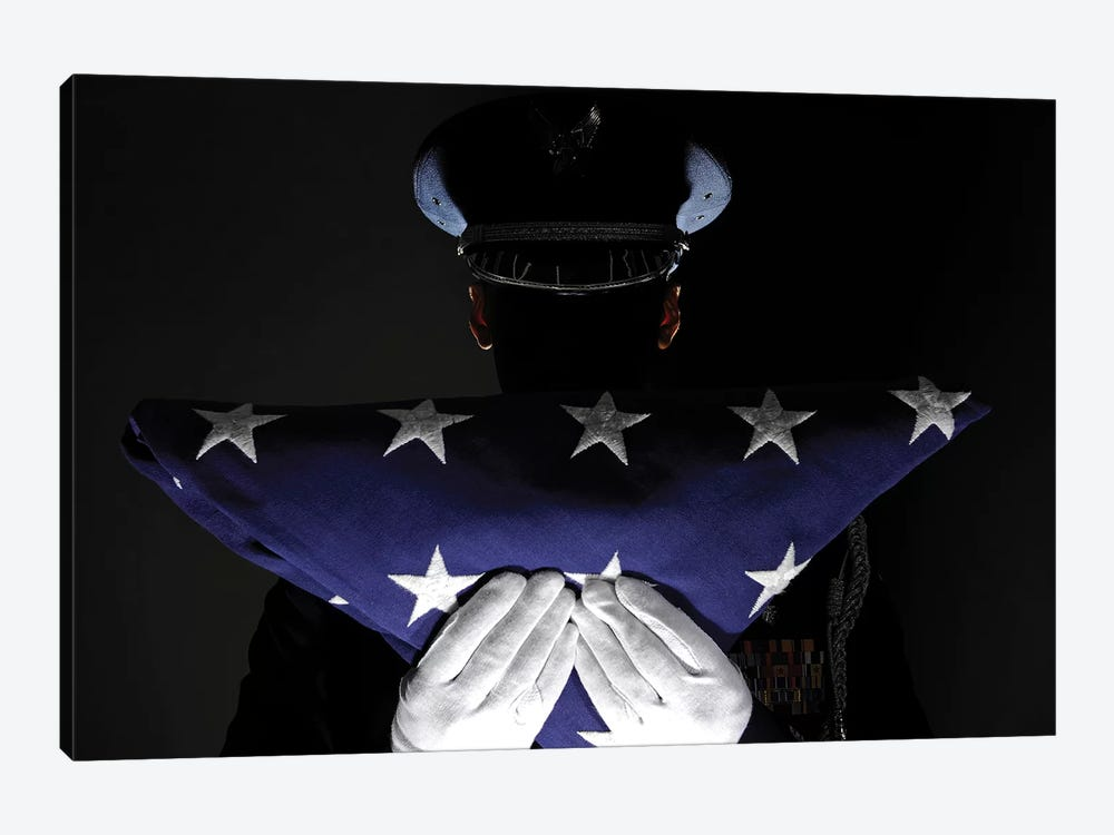 US Airman Stands At Attention After Completing The Flag Dressing Sequence by Stocktrek Images 1-piece Canvas Print