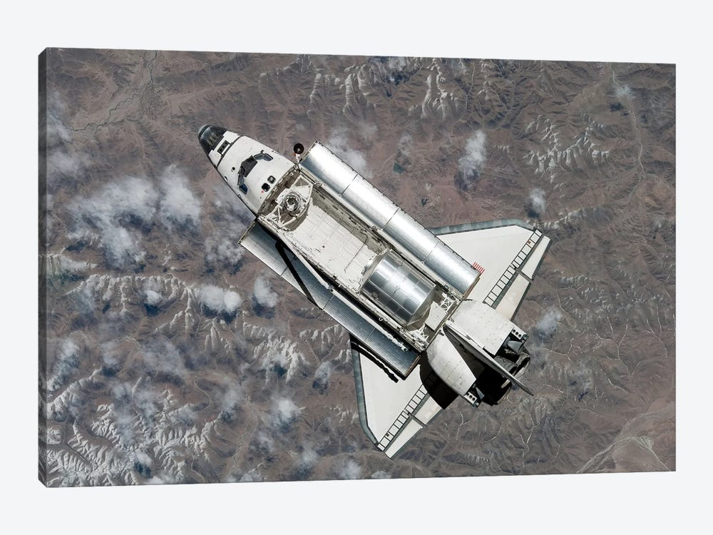 Aerial View Of Space Shuttle Discovery Over Earth As It Approaches The International Space Station by Stocktrek Images 1-piece Canvas Artwork