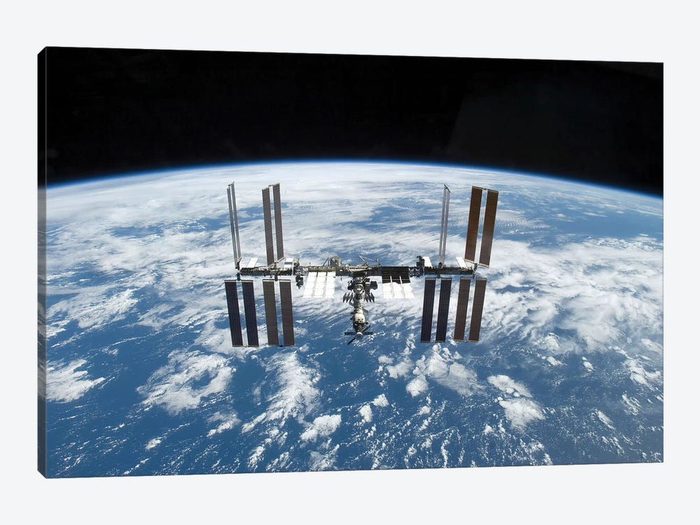 The International Space Station In Orbit Above Earth by Stocktrek Images 1-piece Canvas Wall Art