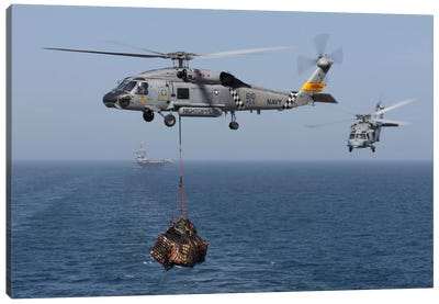 A SH-60J Seahawk Transfers Cargo During A Vertical Replenishment Canvas Art Print