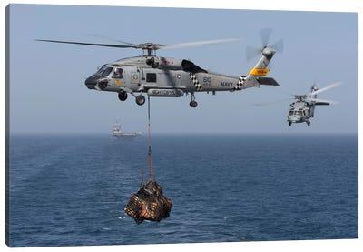 A SH-60J Seahawk Transfers Cargo During A Vertical Replenishment Canvas Art Print