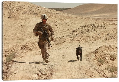 A Dog Handler Walks With An Explosives Detection Dog While On Patrol Canvas Art Print