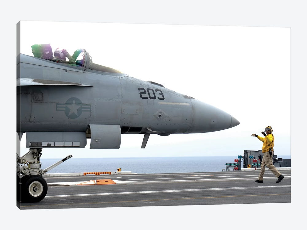 A Sailor Directs An F/A-18E Super Hornet Across The Flight Deck Of USS Nimitz by Stocktrek Images 1-piece Canvas Artwork