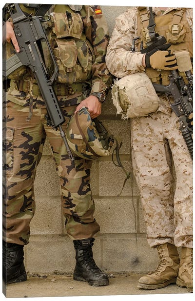 A Spanish Marine And A US Marine Relax Against A Wall Canvas Art Print