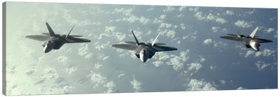 A Three-Ship Formation Of F-22 Raptors Fly Over The Pacific Ocean Canvas Art Print