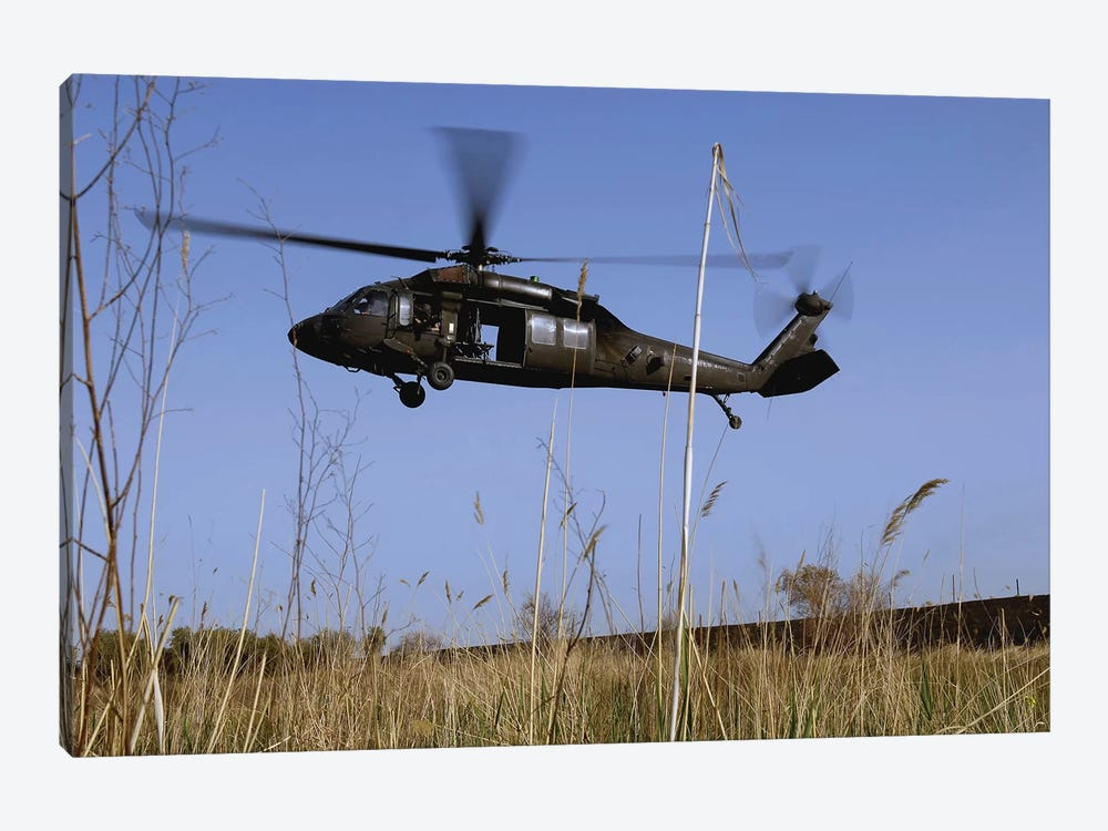 A US Army UH-60 Black Hawk Helicopter Prepares To Pick Up Soldiers by Stocktrek Images 1-piece Canvas Art Print