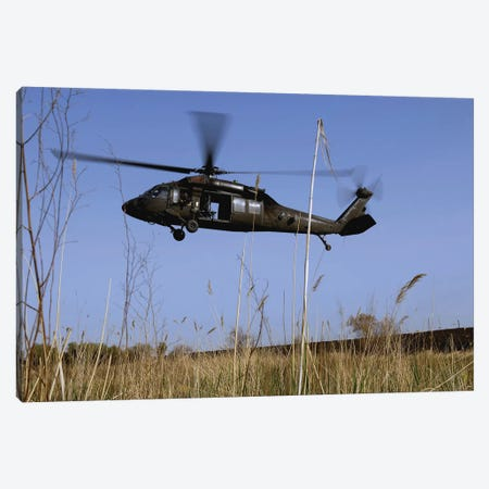 A US Army UH-60 Black Hawk Helicopter Prepares To Pick Up Soldiers Canvas Print #TRK631} by Stocktrek Images Canvas Wall Art