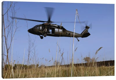 A US Army UH-60 Black Hawk Helicopter Prepares To Pick Up Soldiers Canvas Art Print