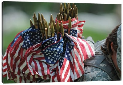 An Army Soldier's Backpack Overflows With Small American Flags Canvas Art Print