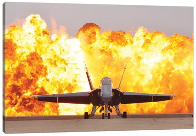 An F/A-18 Hornet Sits On The Flight Line As A Wall Of Fire Detonates Behind It Canvas Art Print
