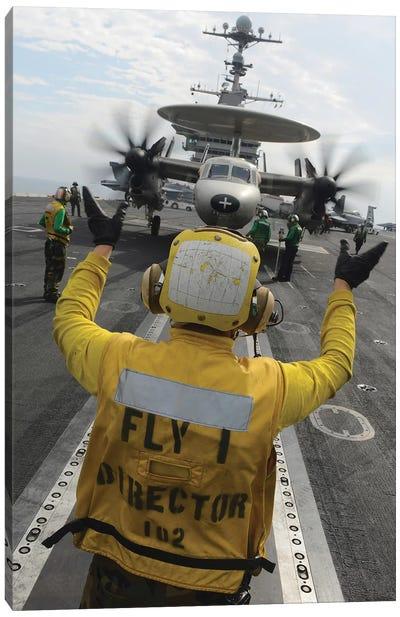 Aviation Boatswain's Mate Directs An E-2C Hawkeye Aboard USS John C. Stennis Canvas Art Print