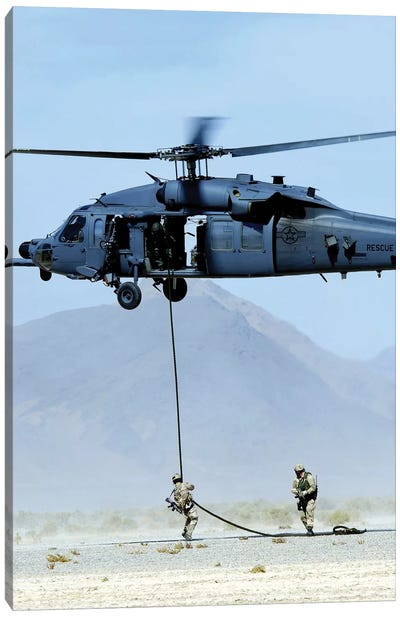 Pararescuemen Descend From An HH-60 Pave Hawk Helicopter Canvas Art Print