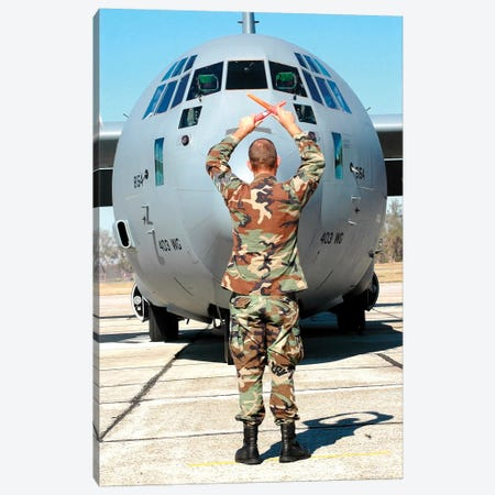 Senior Airman Guides C-130 Hercules Into Its Parking Spot Canvas Print #TRK895} by Stocktrek Images Canvas Art Print