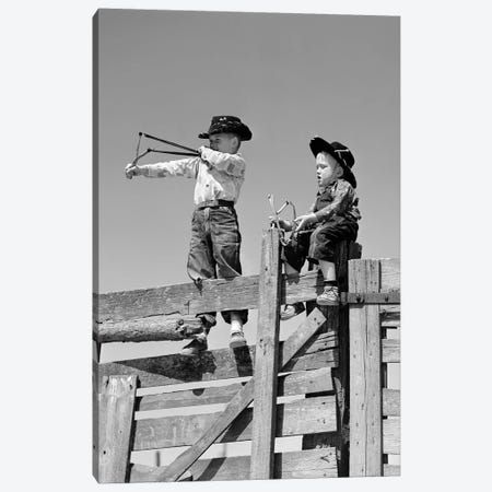 1950s Two Young Boys Dressed As Cowboys Shooting Slingshots On Top Of Wooden Fence Outdoor Canvas Print #VTG361} by Vintage Images Canvas Print