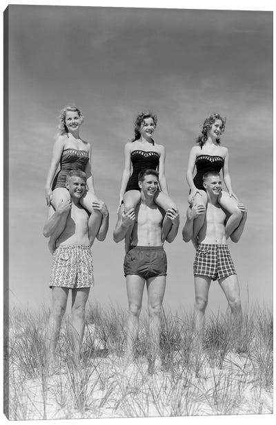 1950s-1960s Three Couples At Beach On Dunes With Women In Identical Bathing Suits Sitting On Men's Shoulders Canvas Art Print