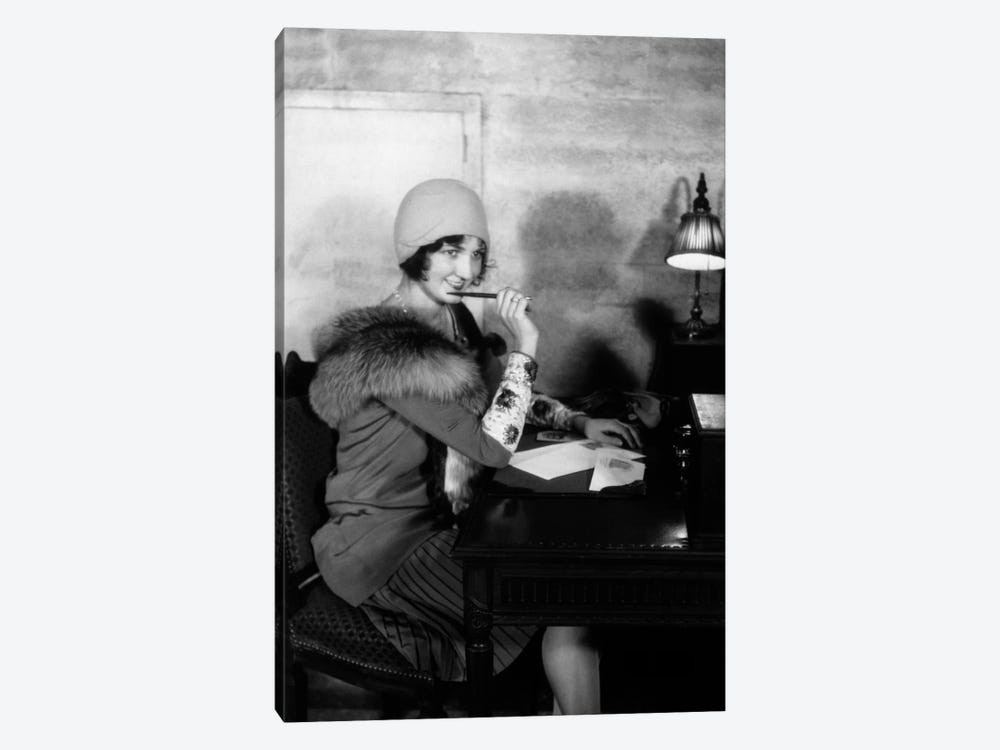 1920s Smiling Woman With Pen To Lips Wearing Cloche Hat And Fur Collar Coat Writing A Letter At Hotel Lobby Desk With Lamp by Vintage Images 1-piece Canvas Print