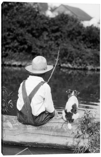 1920s-1930s Farm Boy Wearing Straw Hat And Overalls Sitting On Log With Spotted Dog Fishing In Pond Canvas Art Print