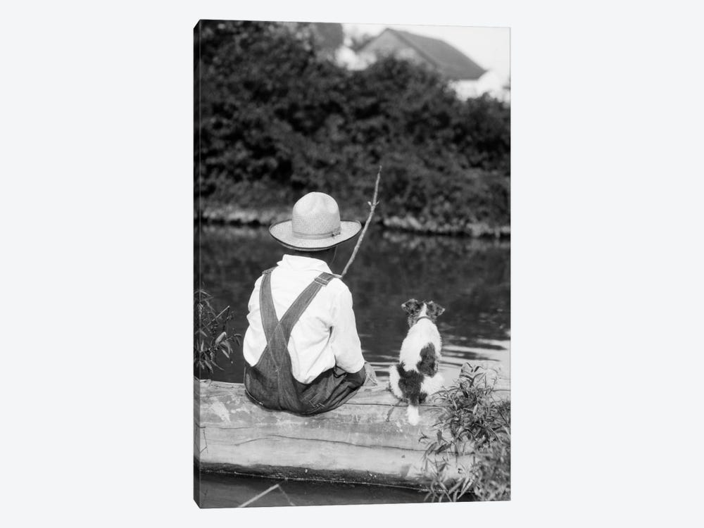 1920s-1930s Farm Boy Wearing Straw Hat And Overalls Sitting On Log With Spotted Dog Fishing In Pond by Vintage Images 1-piece Canvas Art Print